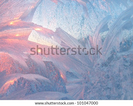 ice patterns and morning sunlight on winter glass