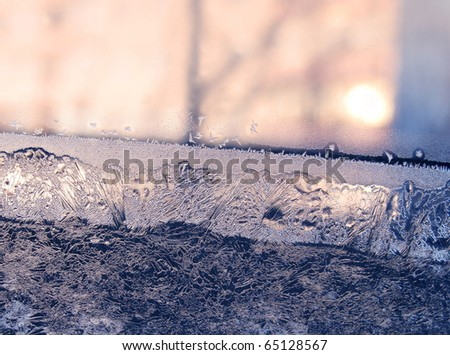 ice patterns and sunlight on winter window - stock photo