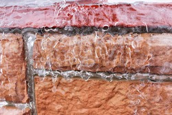 Ice rain problem. Icing a brick wall of a house close up. Frozen drops form a continuous crust cause wet snow.