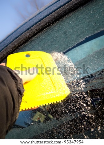 Ice scraper on car window