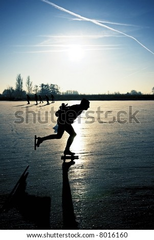 Ice skater at sunset on frozen ice in the fields of the Netherlands