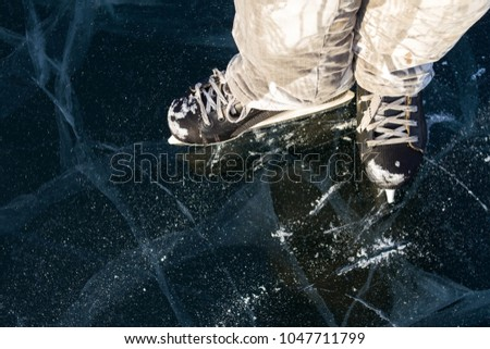 Ice skater's skates covered with snow on the picturesque ice of Lake Baikal in winter during a bright sunny day. #1047711799