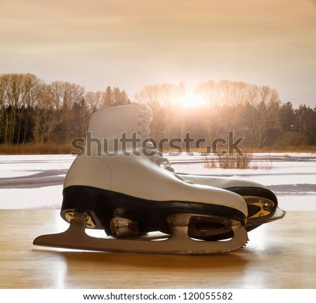 Ice skates on wooden table against frozen lake landscape