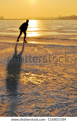 Ice skating - Ice skater at sunset on frozen lake in the Netherlands