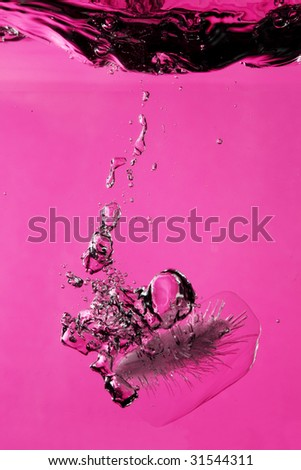 Ice splashing on water against pink background
