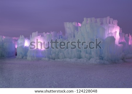Ice structure illuminated with pink lights behind ice walls and layers of icicles