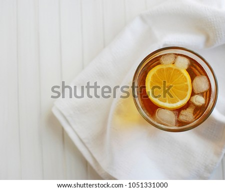 Ice tea with lemon. Top view on white napkin and white wooden table. #1051331000