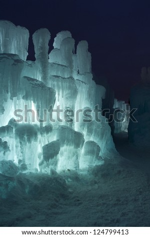Ice tower and passageway illuminated with aquamarine colored LED and decorated with icicles at night