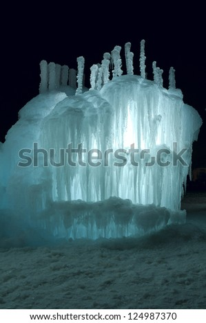 Ice tower and sculpture  illuminated with aquamarine colored LED lights and decorated with icicles at night
