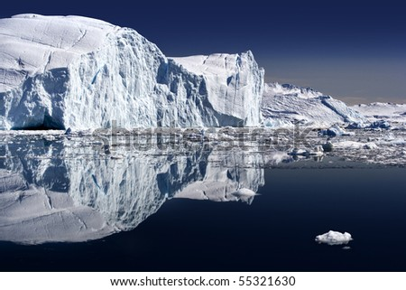 Iceberg and its reflexion in still water
