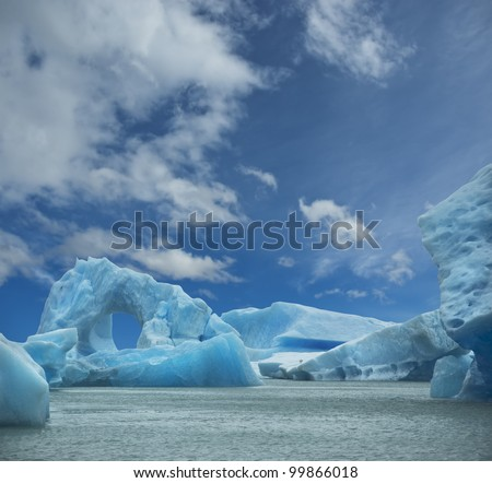 Iceberg floating in the water forming an arch. El Calafate, Argentina.