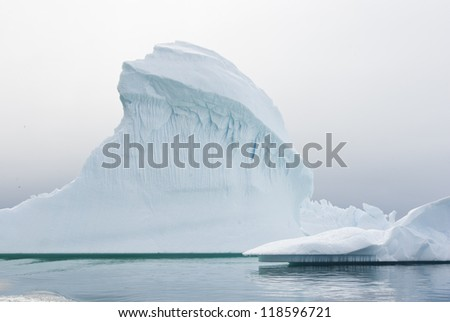 Iceberg in Antarctic waters on a cloudy summer day.
