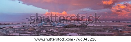 Iceberg lagoon in Fjallsarlon, Iceland. Panoramic view of beautiful sunset light, concept of global warming and ice melting.