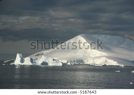 Icebergs and snow covered mountain, with blue sky & Calm seas.Petermann Island,Antarctica