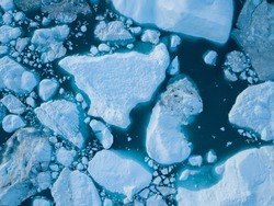 Icebergs drone aerial image top view - Climate Change and Global Warming. Icebergs from melting glacier in icefjord in Ilulissat, Greenland. Arctic nature ice landscape in Unesco World Heritage Site.