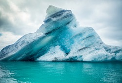 Icebergs floating.  Ices and icebergs. Glacier lagoon. Greenland iceberg. Melting ice. South coast Iceland. Jokullsarlon glacier lagoon. Volcanic ash on the ice. Ice age glacier. Melting iceberg.