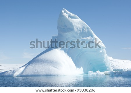 Icebergs in the sunny bright light on the background of the island.