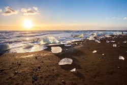 Icebergs on the cost of the black sand beach in the rays of the rising sun,  Jokulsarlon,  south Iceland.