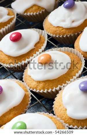 Iced buns on a tray with coloured sweet tops