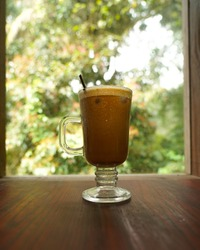 Iced cappuccino, served in a legged glass, served on a wooden table next to the window with a view of the garden with trees and flowers.