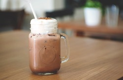 Iced chocolate topped with coco flavor and whipped cream served on desert coffee shop cafe' wooden table. Restaurant table atmosphere.