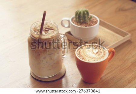 iced coffee and cappuccino latte art with cactus in coffee shop vintage color tone