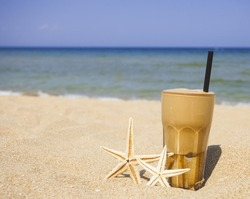 Iced coffee and starfishes on a sandy beach background