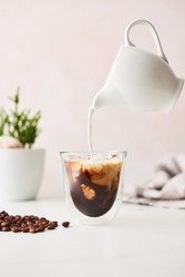 Iced coffee in a double walled glass with latte poured over from floating milk jug. Feminine with copy space. High resolution image.