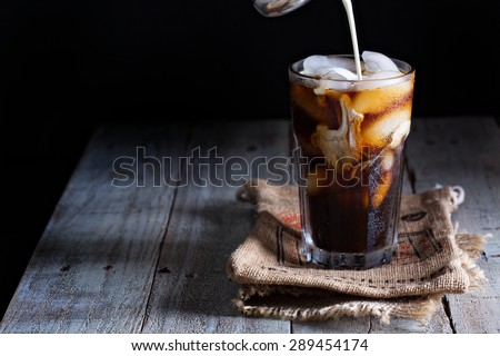 Iced coffee in a tall glass with cream poured over #289454174