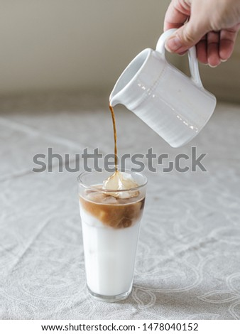 Iced coffee latte poured into a tall glass of milk with ice cubes on a clean and nice table, vintage, rustic, minimalistic look, light pouring, morning #1478040152