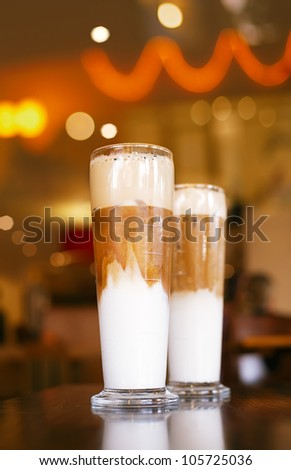iced coffee latte with lights on background in a tall glasses, shallow dof