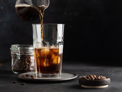 Iced coffee, process of making. Pouring coffee into glass with ice cubes. Cold and refreshing beverage, soft drink. Dark background. Copy space.