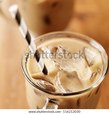 Iced coffee with black striped paper straw closeup