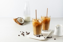 Iced coffee with coconut milk in a tall glass on white wooden table. Cold refreshment summer drink.