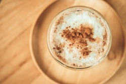 Iced coffee with milk froth on top with cinnamon powder on wood table