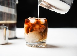 Iced cold brew coffee in a glass with milk poured over.