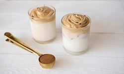 Iced frothy Dalgona Coffee, a trendy fluffy creamy whipped coffee. Korean drink latte espresso with coffee foam. cups and spoon with instant coffee and sugar.