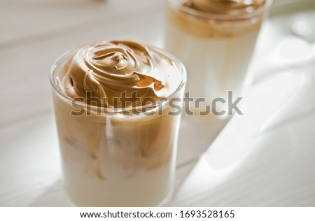Iced frothy Dalgona Coffee, a trendy fluffy creamy whipped coffee. Korean drink latte espresso with coffee foam. made of instant coffee, sugar, hot water and milk. close up view.