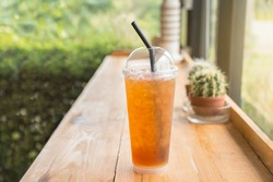 Iced lemon tea in a tall plastic cup on the wooden table.