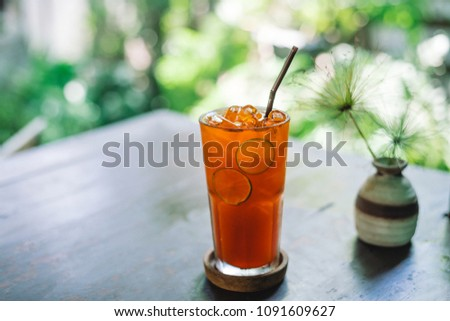 Iced lemon tea on outdoor wooden table with blur outdoor garden background