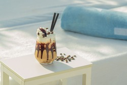 iced mocha coffee in front of a white background. cold coffee on the beach club in hot summer day. Coffee image with cream and foam on the background with coffee beans, sun beds and towels, holiday.