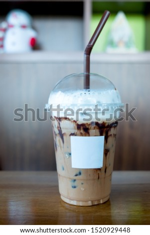 Iced mocha coffee with shower chocolate sauce in glass. Cold summer drink with tubes #1520929448