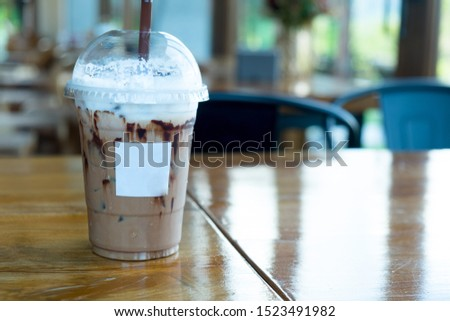 Iced mocha coffee with shower chocolate sauce in glass. Cold summer drink with tubes #1523491982