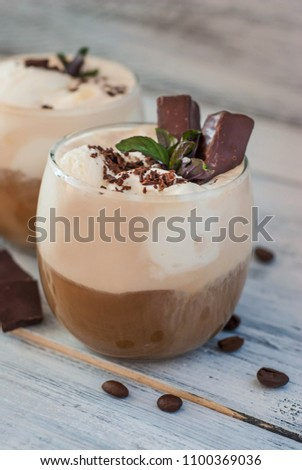 Iced mocha coffee with whip cream. Summer drinking times. Coffee beans. Rustic textured wooden background.  #1100369036
