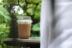 Iced Mocha in transparent plastic glass on table's corner, selective focus on glass with blurred background of garden and blurred foreground of someone in white T-shirt.