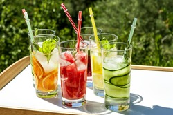 Iced summer drink. Refreshing multicolored alcol-free cocktails in glasses with straws. Watermelon,cucumber, lemon, orange, strawberry cocktail on white tray on nature background with tropical trees.