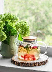 Iced tea with mint, lemon, apple, red currant in a glass teapot and a bouquet of hydrangeas in a ceramic jug on the window in a bright cozy room