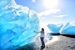 Iceland Amazing landscape at Iceberg beach. Tourist by icebergs on Ice beach, Breidamerkursandur aka Diamond Beach by jokulsarlon glacial lagoon / glacier lake nature. Woman in icelandic sweater.