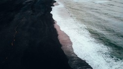 Iceland Black Sand Beach with wave and sunset lights.