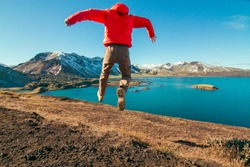 Iceland experiential travel photography, young active man leaping with beautiful snow covered mountains and lake in the background